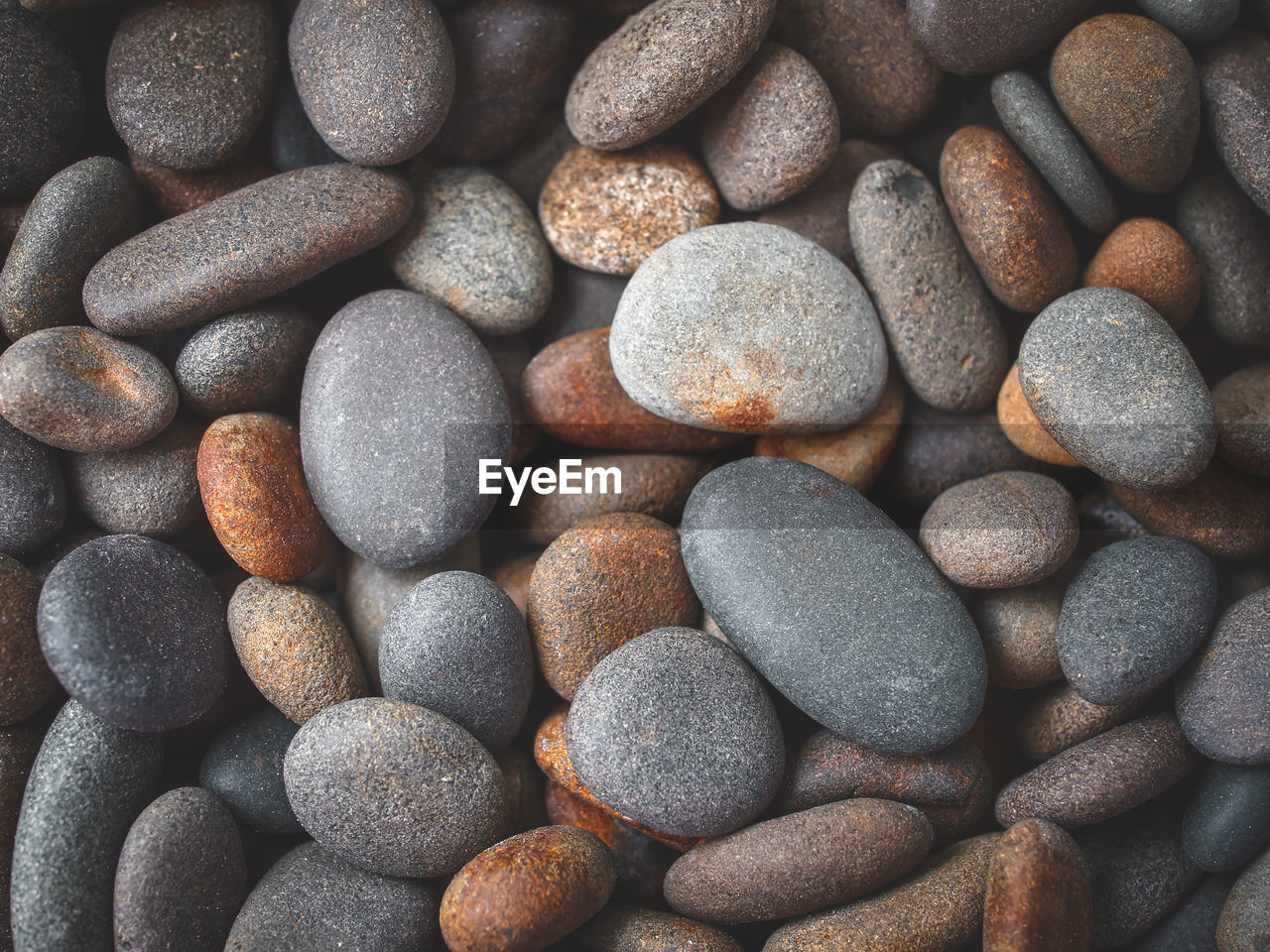 Top view of river pebbles, used as wallpaper or background.