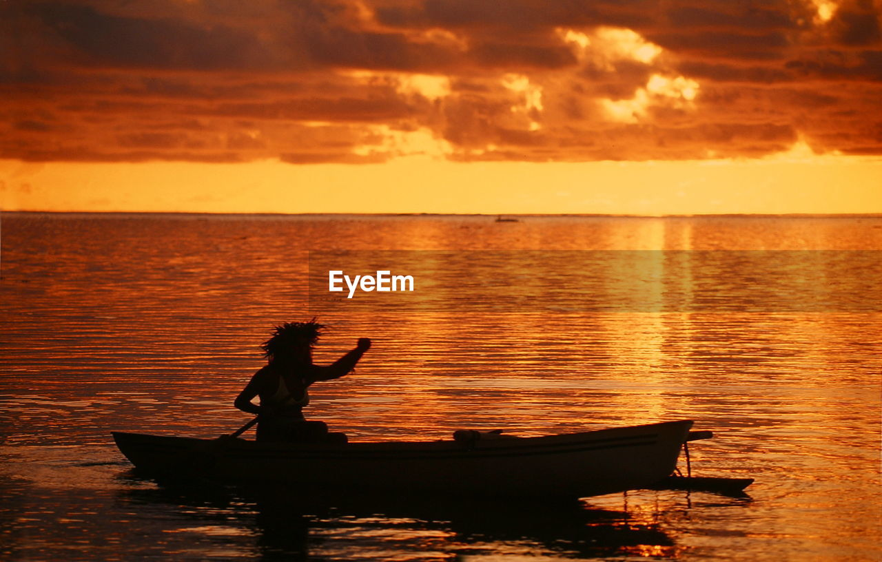 Woman Paddling On Sea At Sunset