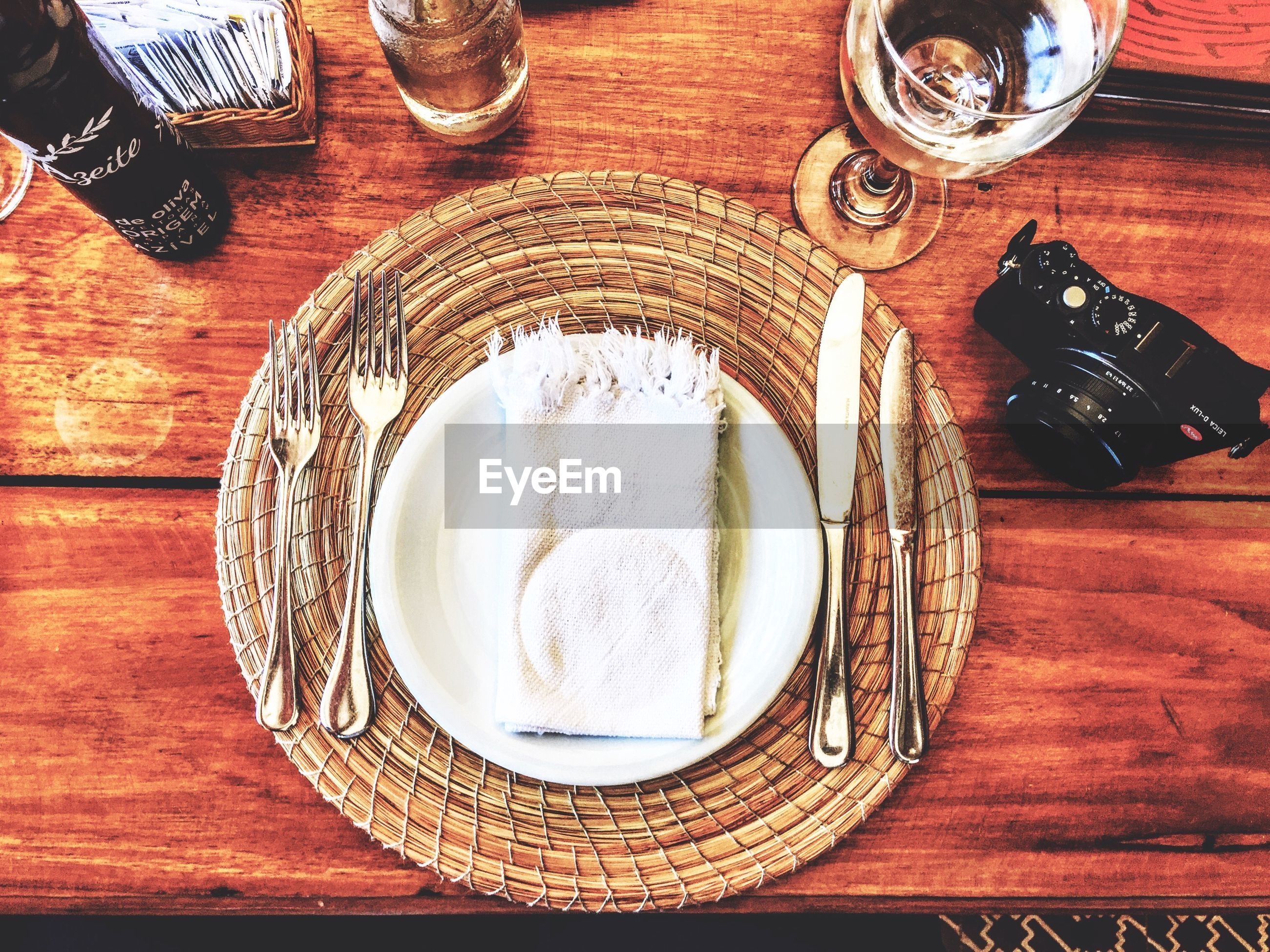 Plate with forks and table knife on place mat by camera