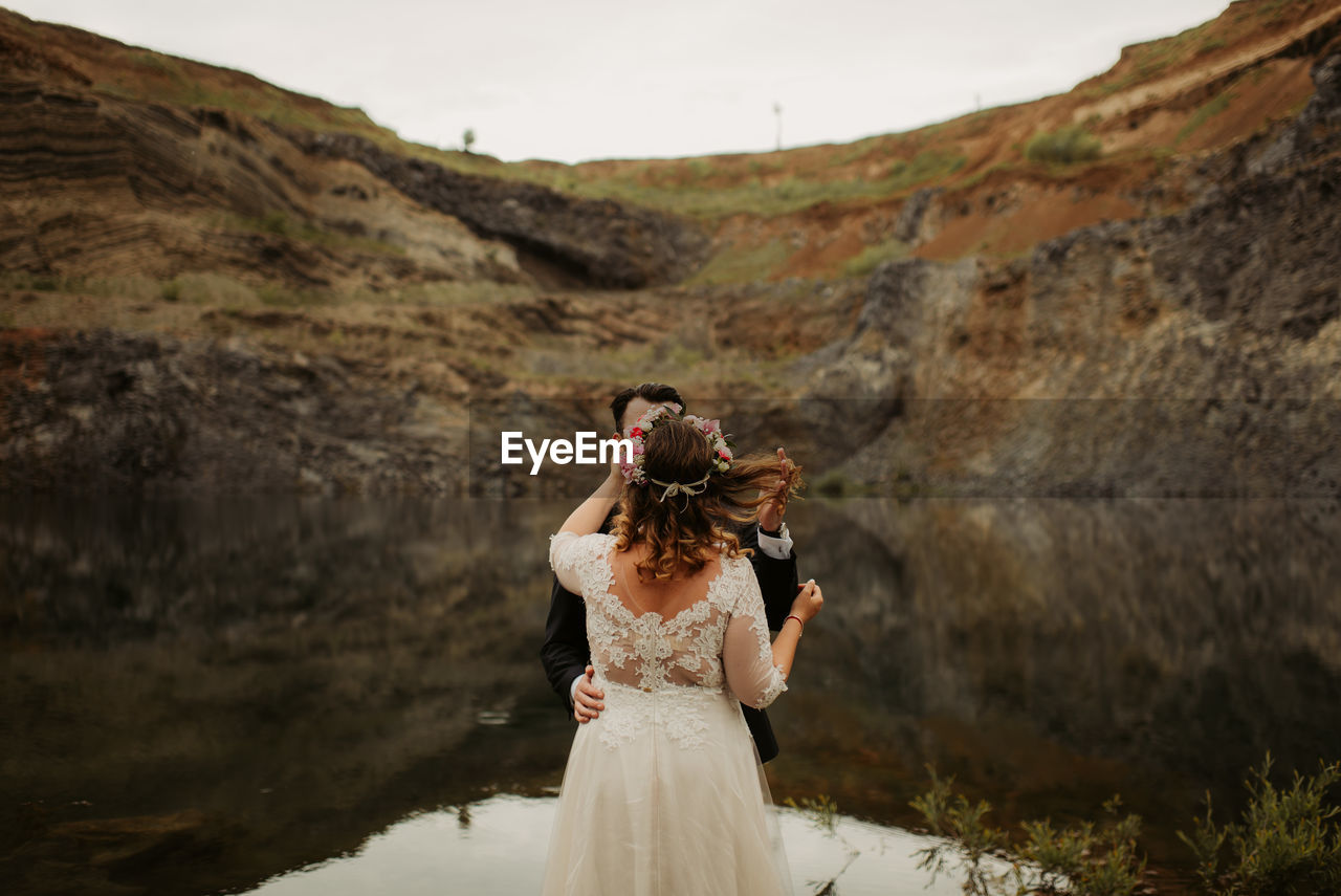 Wedding Couple Standing By Lake Against Mountain