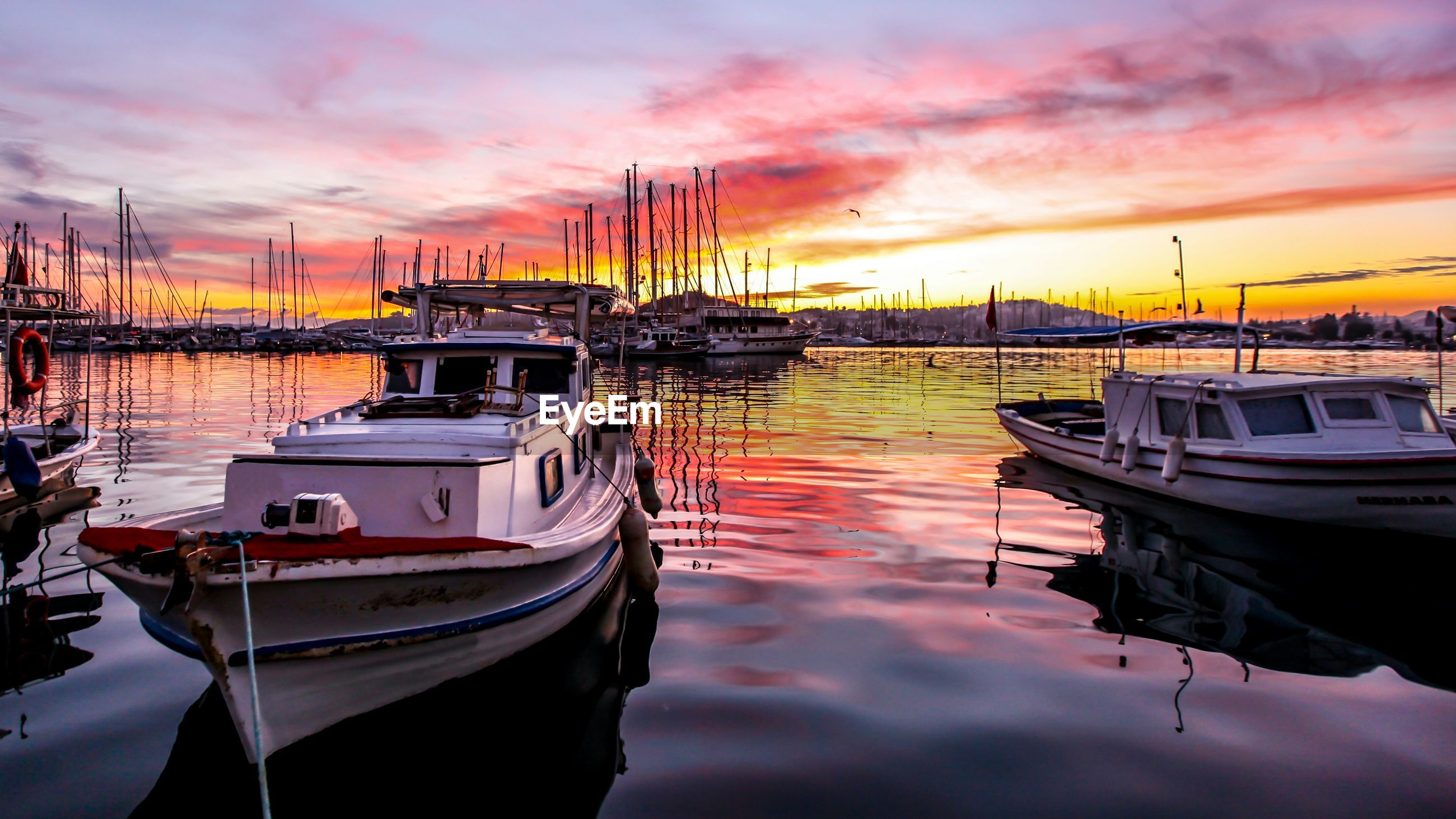 Boats moored at river against cloudy sky during sunset