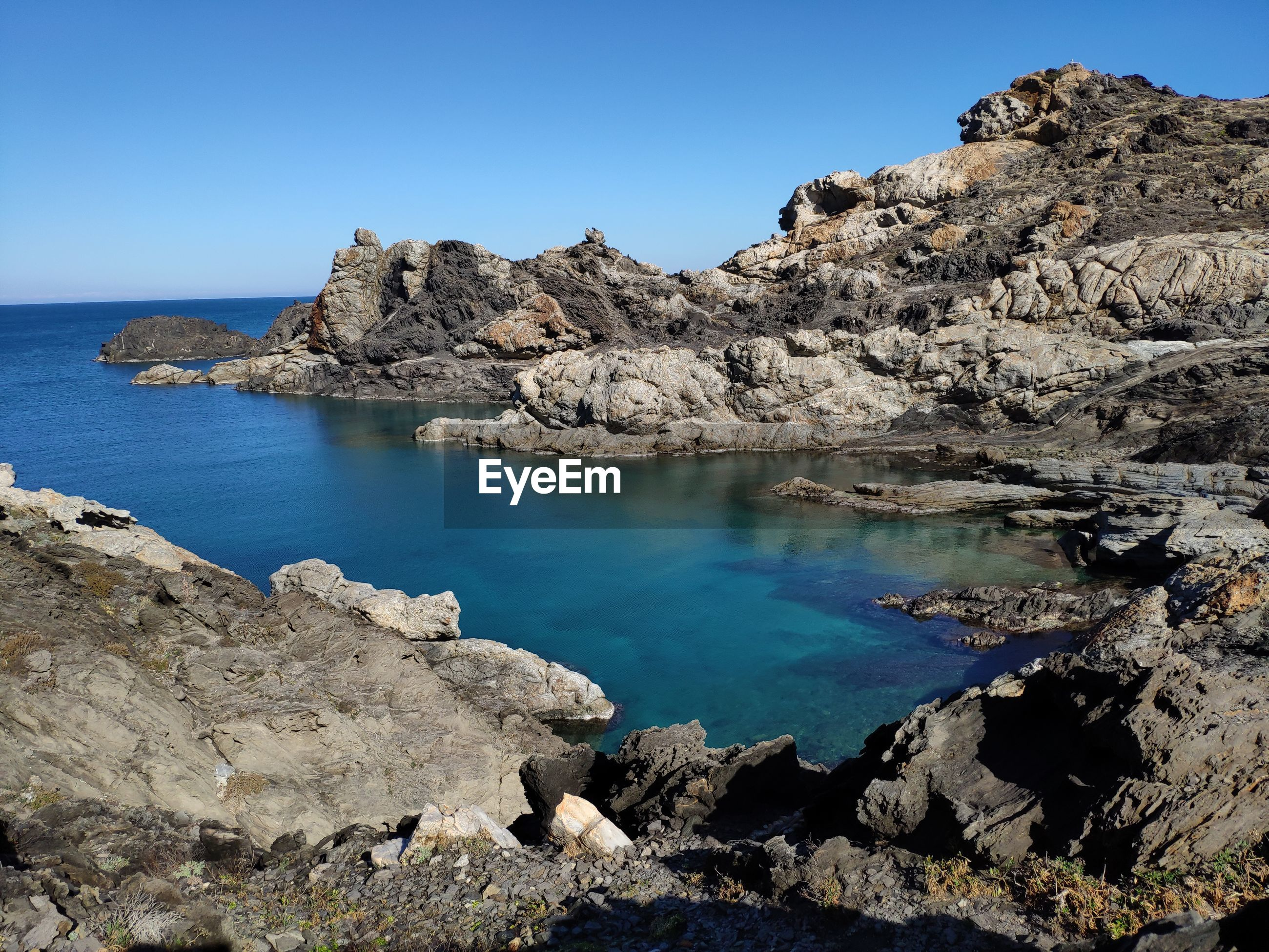 Scenic view of rocks in sea against clear blue sky