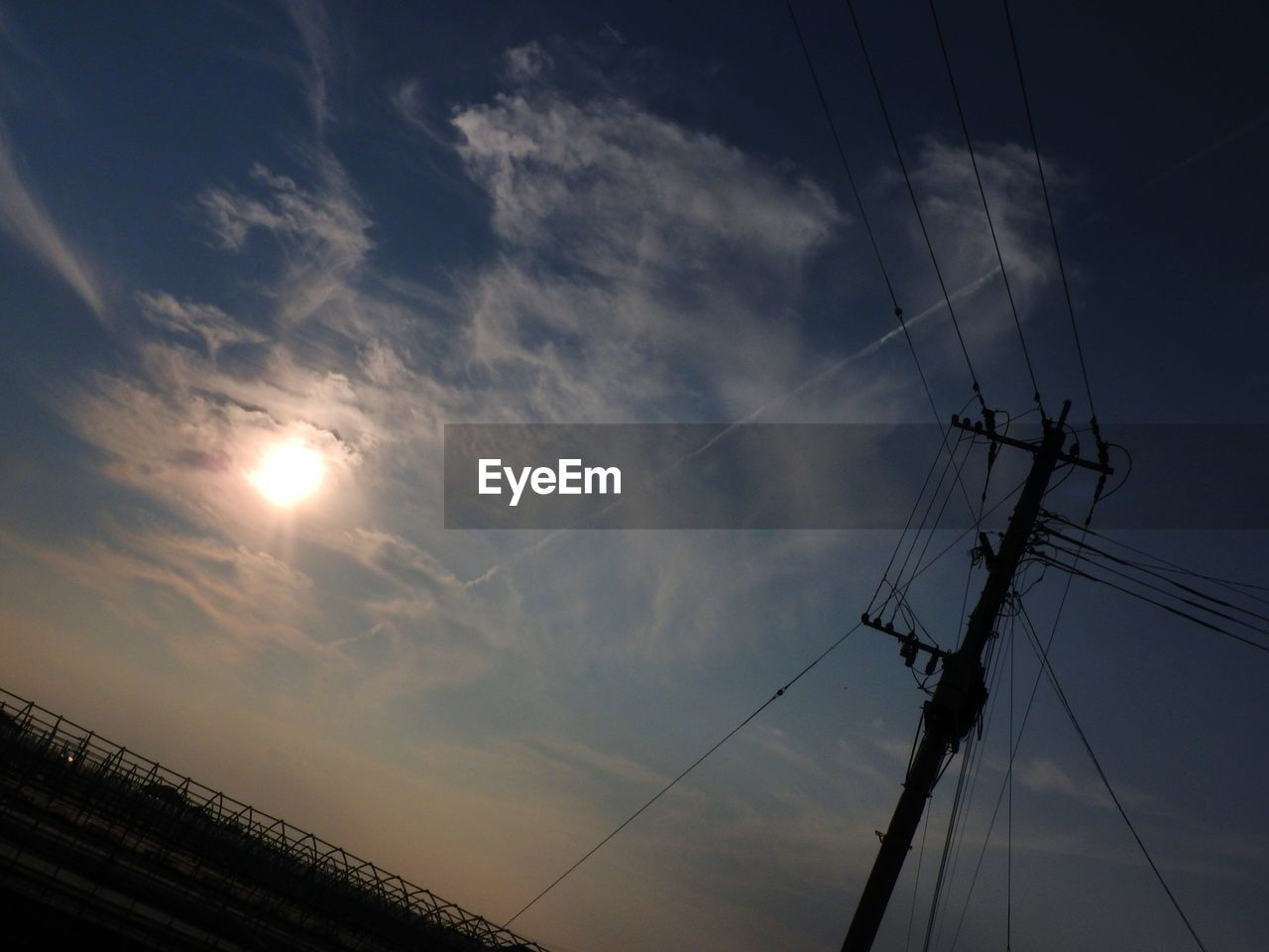 cable, connection, electricity, low angle view, sky, fuel and power generation, power line, power supply, technology, sun, electricity pylon, outdoors, no people, cloud - sky, sunset, day, nature, vapor trail