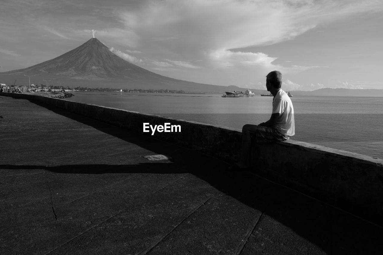 Man watching smoke eruption from volcanic mountain peak at waterfront