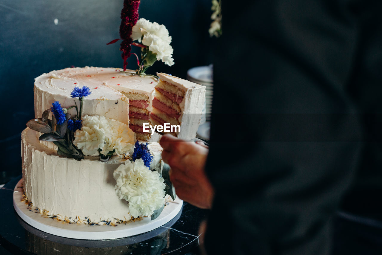 Midsection Of Man Taking Cake Slice At Wedding Ceremony