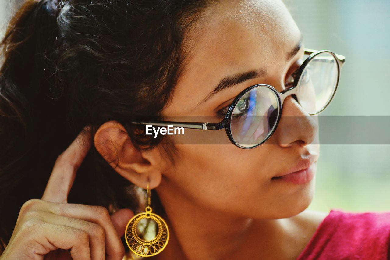 Close-Up Of Woman Wearing Eyeglasses And Earring