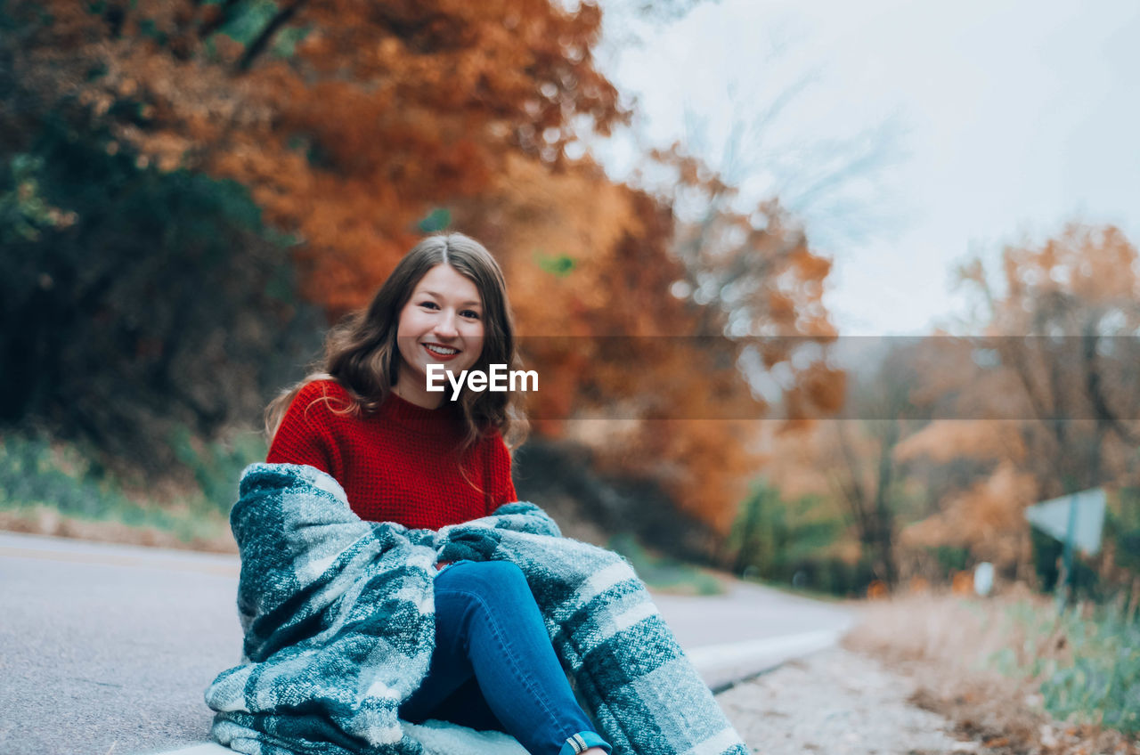 Portrait of smiling girl sitting by road during autumn