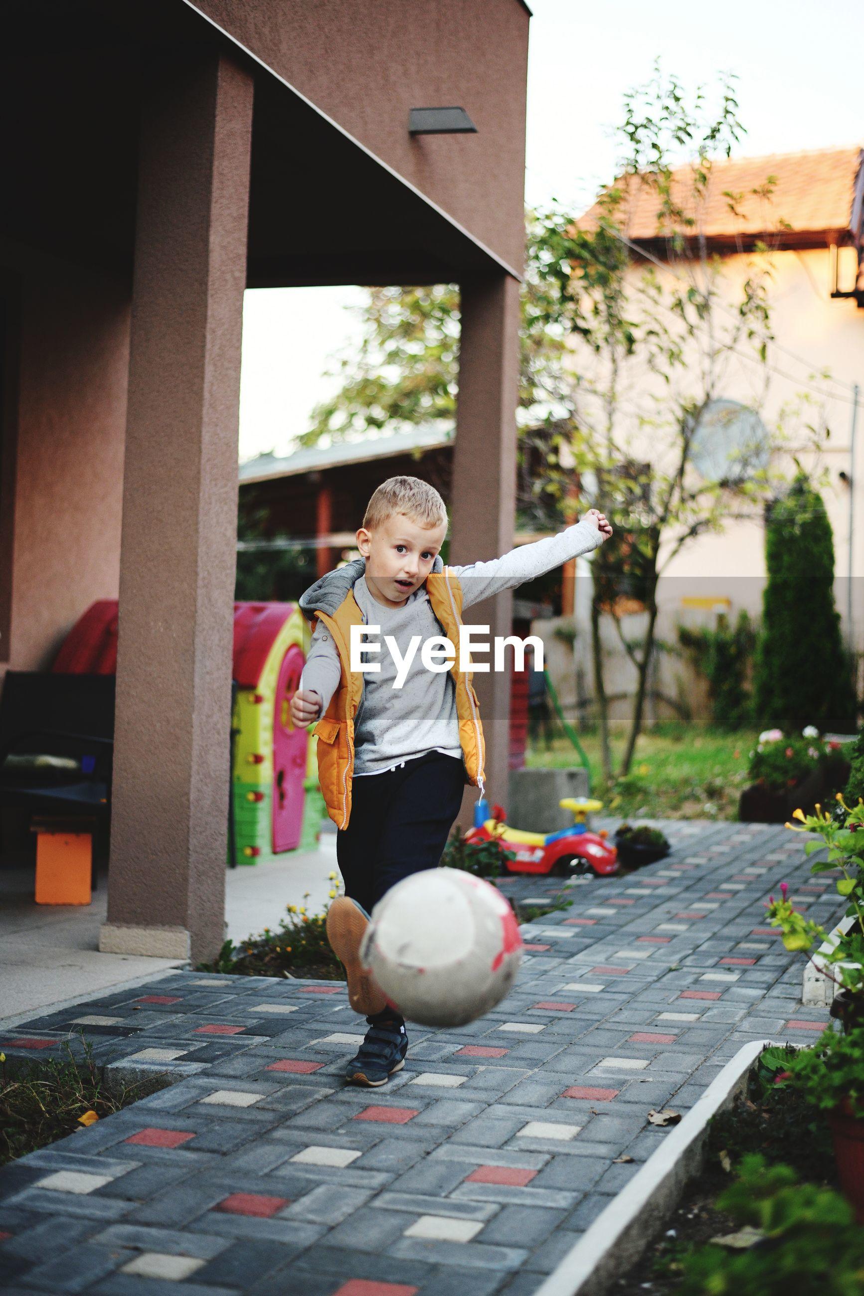 Full length portrait of cute boy kicking ball outside house