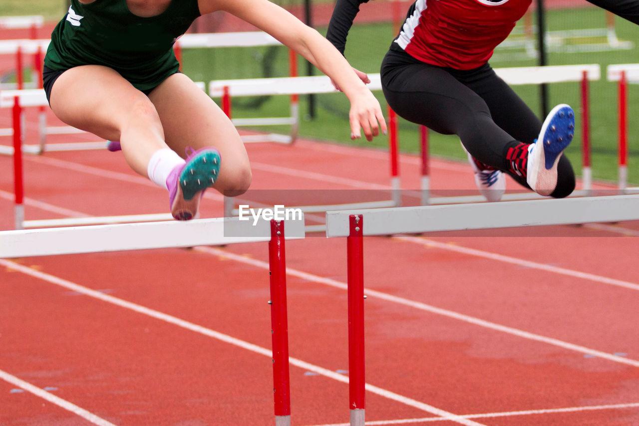 Female athletes hurdling on sports track