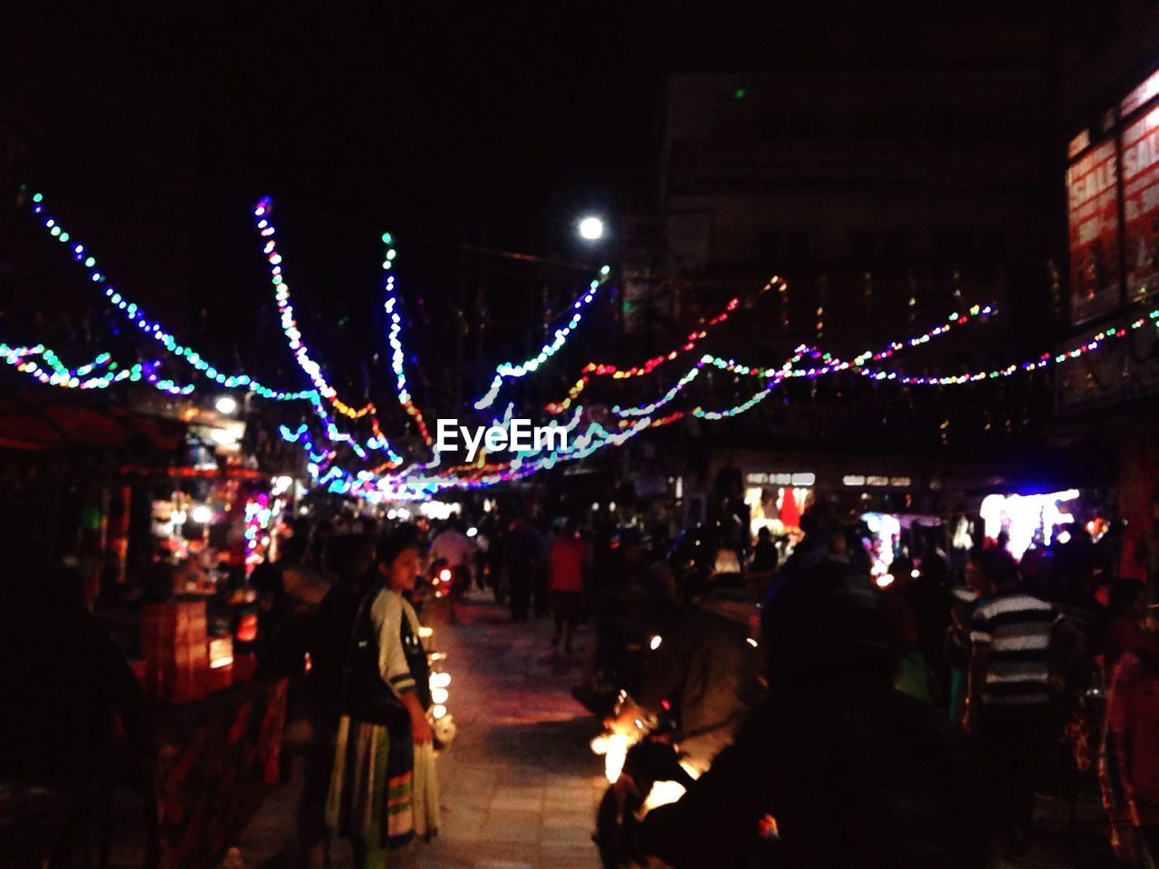 night, illuminated, celebration, built structure, real people, large group of people, architecture, lighting equipment, city, building exterior, lifestyles, leisure activity, city life, christmas, men, women, christmas lights, market, outdoors, crowd, christmas decoration, sky, people