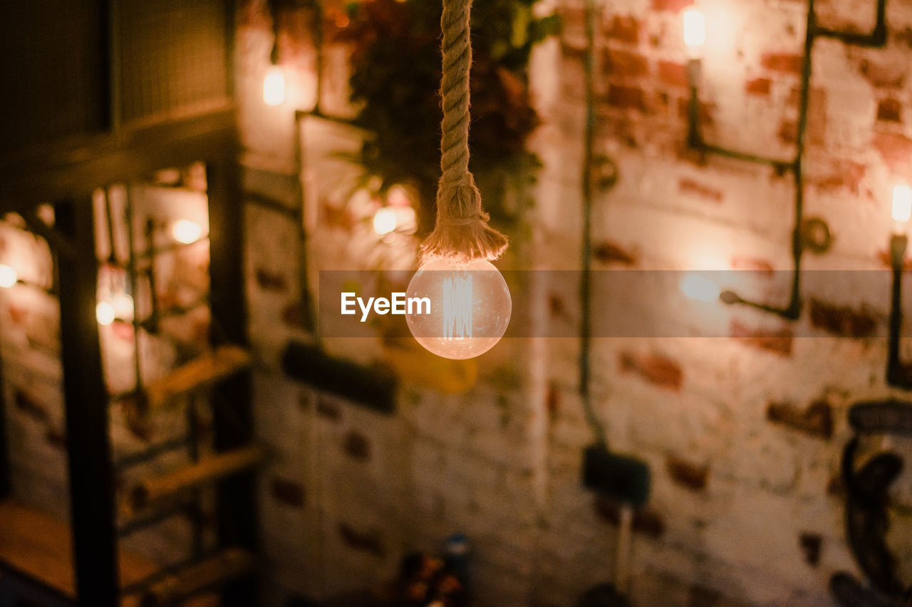 Close-Up Of Illuminated Light Bulb Hanging On Rope At Night