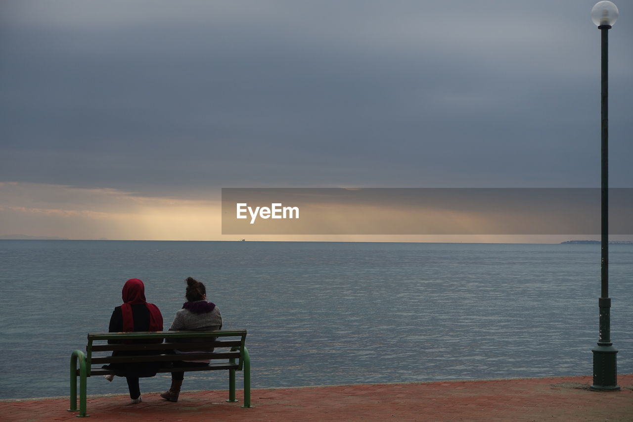 Rear view of friends sitting on bench by sea against cloudy sky