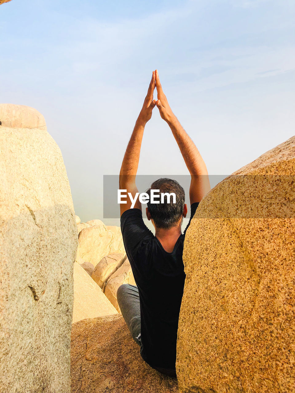 Rear view of man with arms raised meditating while sitting on rock against sky