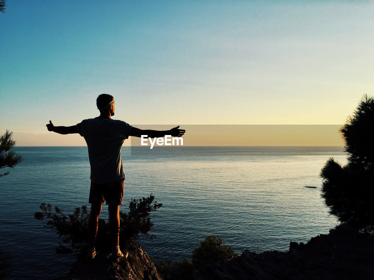 water, sky, sea, scenics - nature, standing, beauty in nature, one person, real people, leisure activity, lifestyles, sunset, human arm, tranquility, arms outstretched, limb, nature, tranquil scene, non-urban scene, horizon over water, outdoors, arms raised