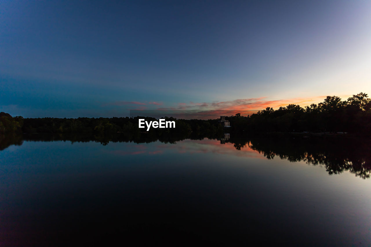 Scenic View Of Calm Lake With Reflection During Sunset