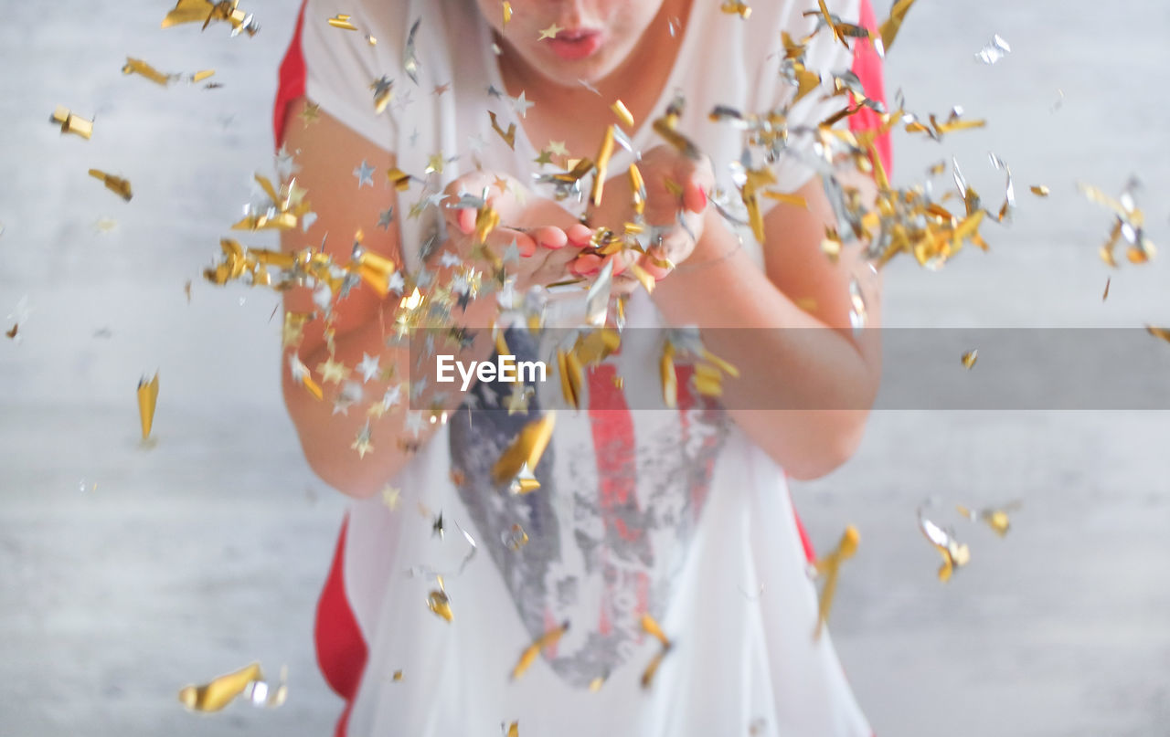 Midsection Of Teenage Girl Blowing Confetti