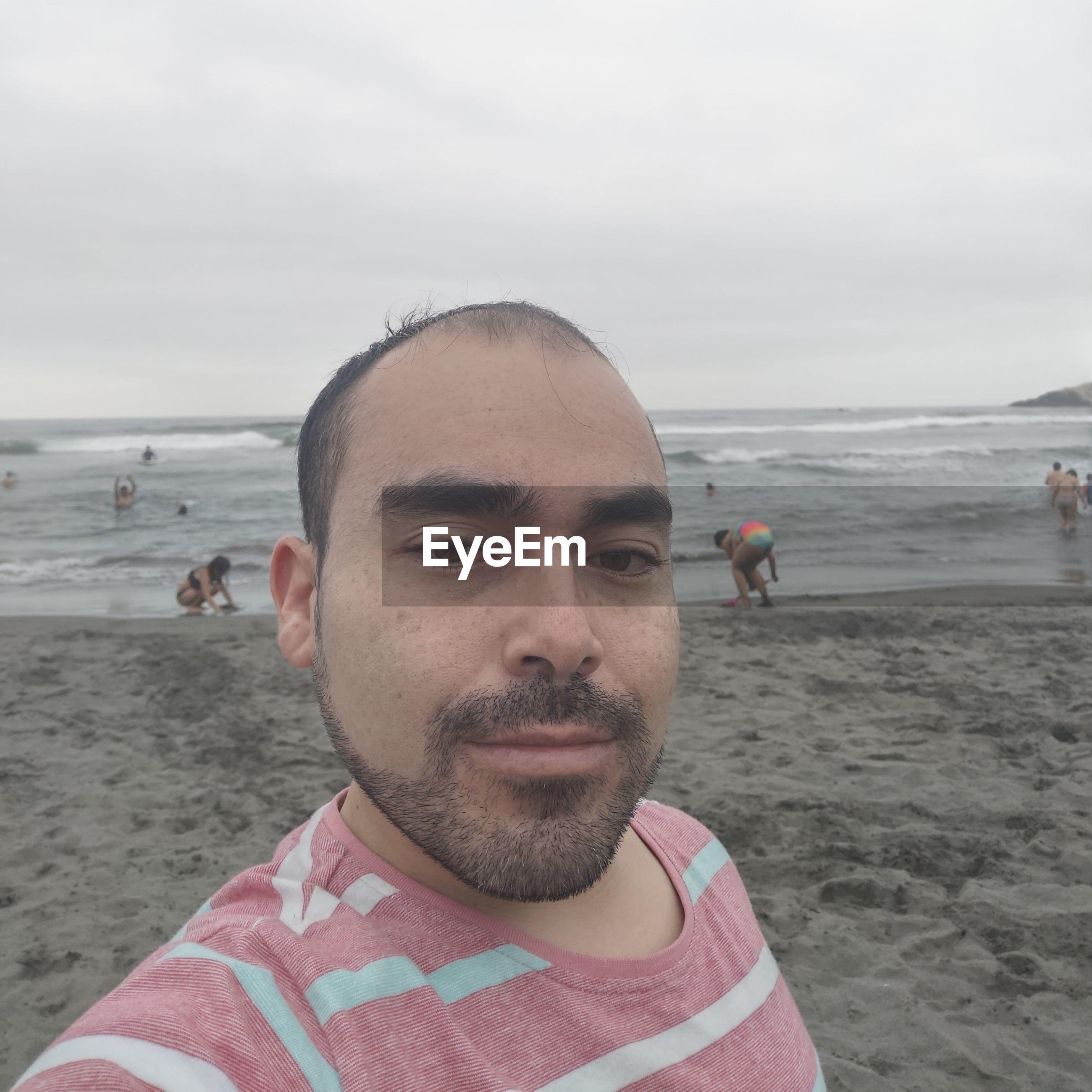 Portrait of mature man on beach against sky
