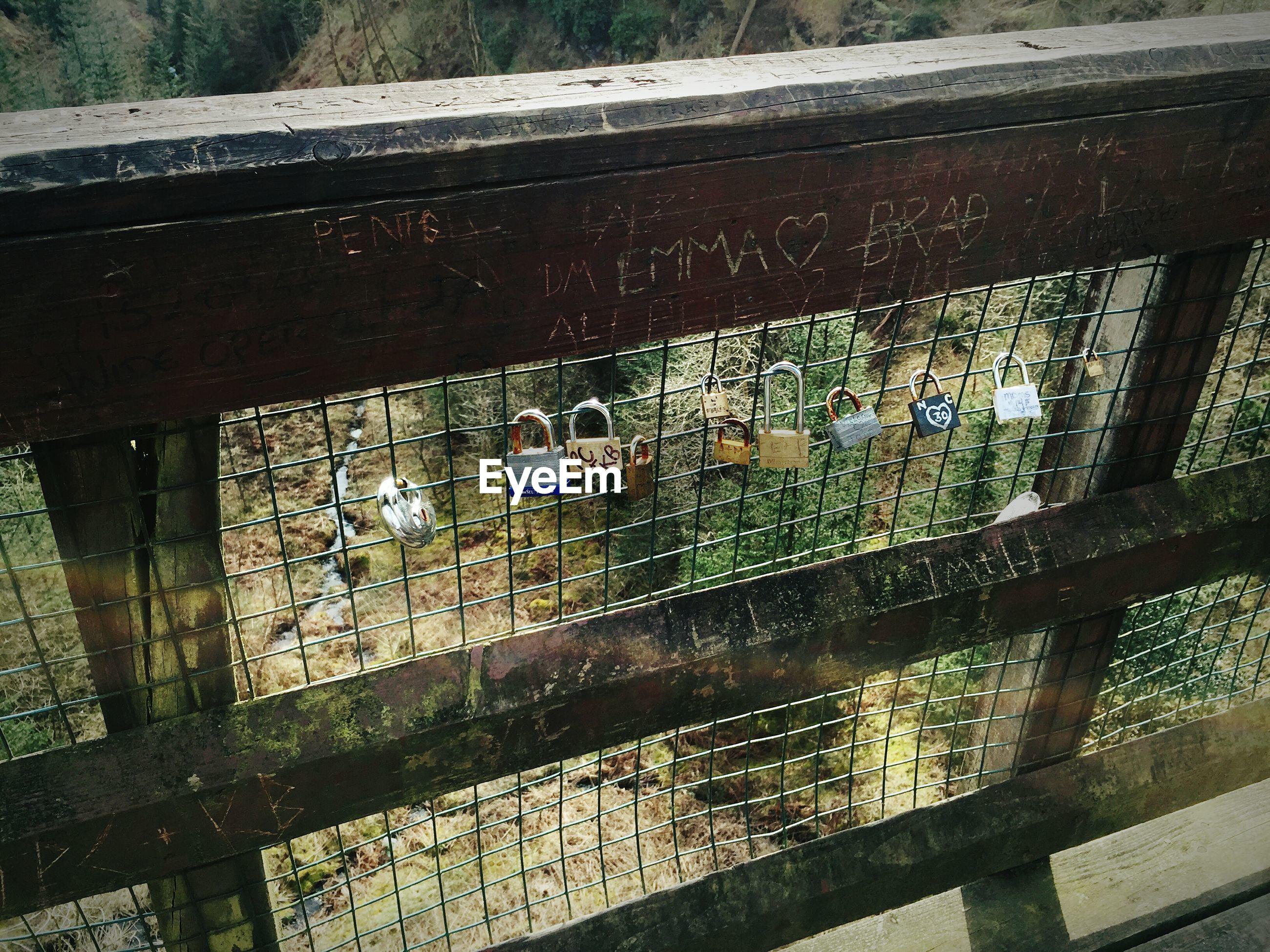 High angle view of padlocks on railing of bridge