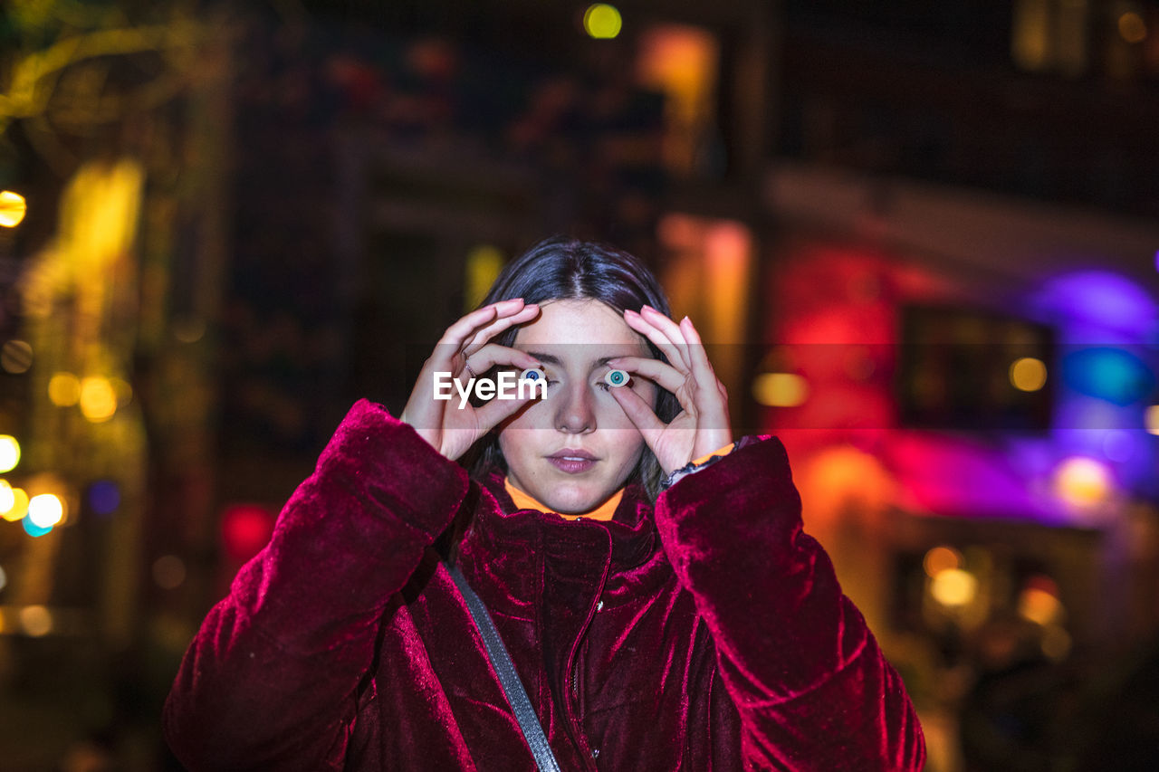 portrait, one person, front view, headshot, night, looking at camera, clothing, lifestyles, focus on foreground, real people, illuminated, young adult, warm clothing, young women, winter, standing, leisure activity, scarf, teenager