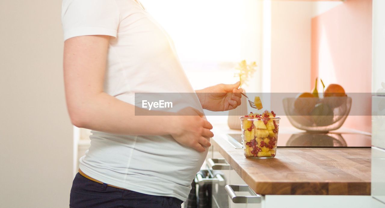 Midsection Of Pregnant Woman Standing By Fruits On Kitchen Counter