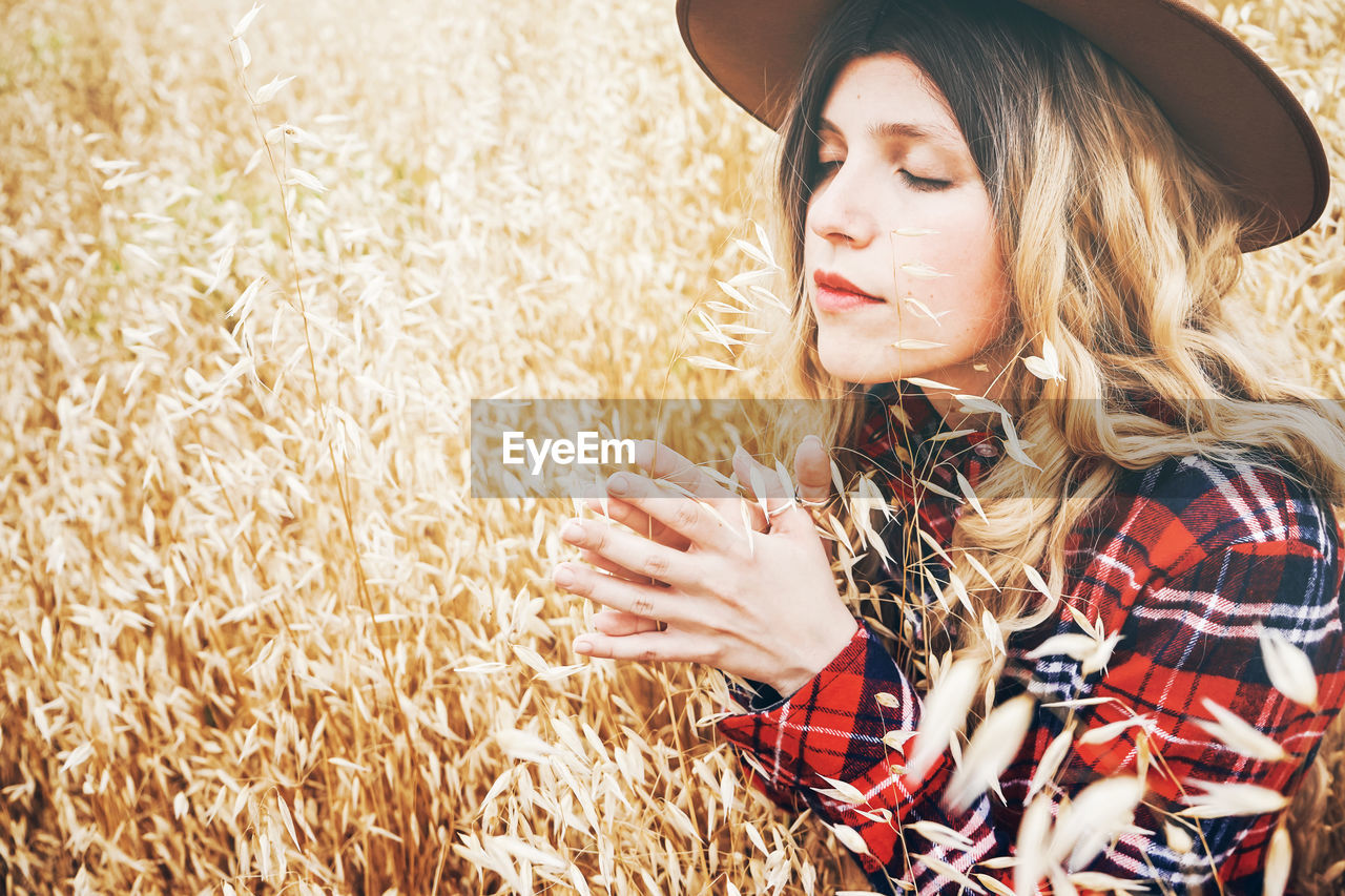 one person, young adult, hat, young women, hair, lifestyles, farm, clothing, adult, real people, leisure activity, plant, agriculture, hairstyle, crop, beauty, day, casual clothing, beautiful woman, outdoors