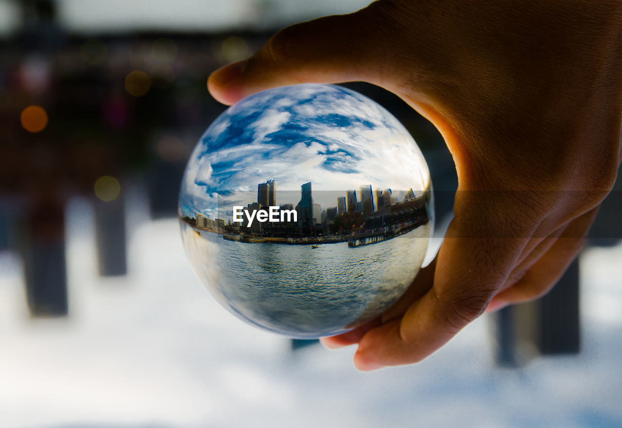 Cropped hand holding crystal ball with reflecting of modern buildings against sky