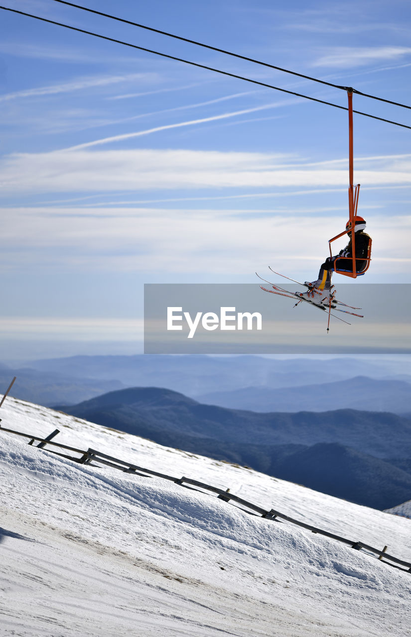Man Sitting On Overhead Cable Car In Mountains