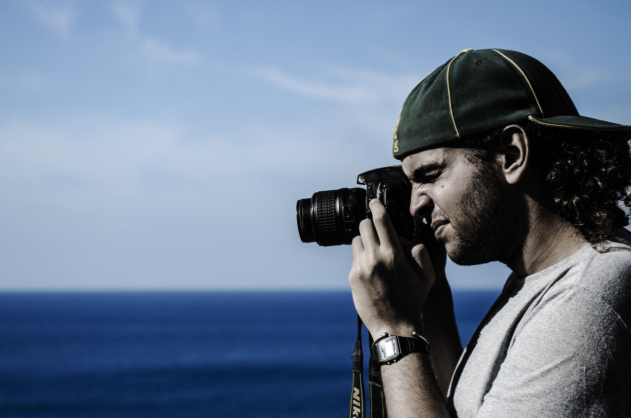 real people, camera - photographic equipment, sea, photography themes, photographing, water, one person, outdoors, holding, leisure activity, headshot, sky, lifestyles, day, photographer, men, technology, nature, young adult, digital single-lens reflex camera, close-up