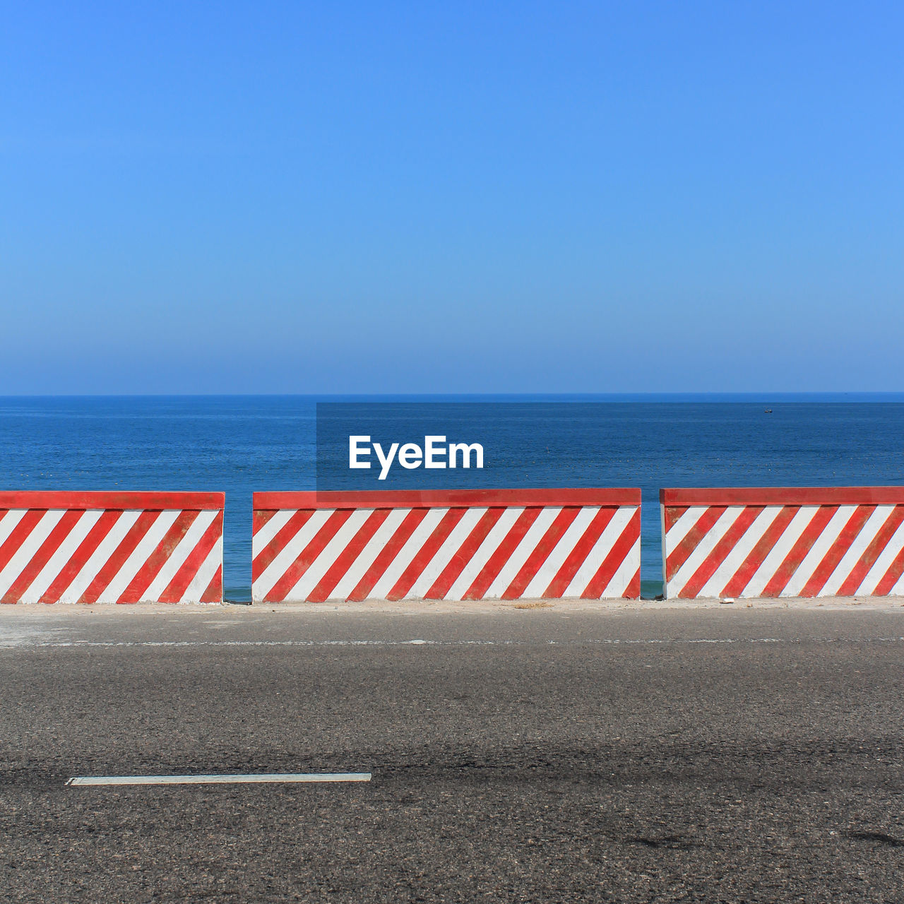 Striped Retaining Wall On Road By Sea Against Clear Sky