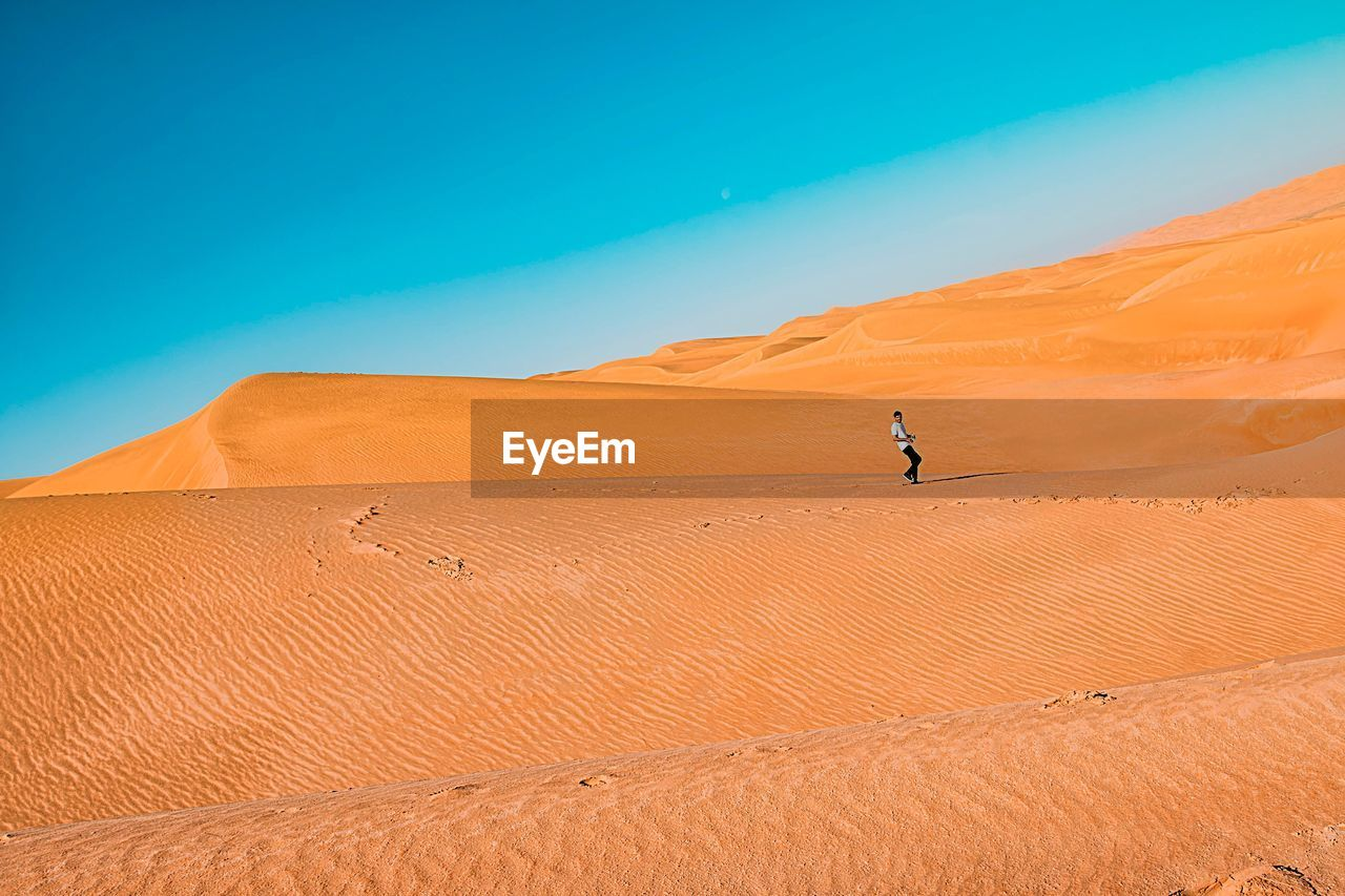 desert, sand dune, arid climate, sand, extreme terrain, nature, landscape, one person, real people, outdoors, non-urban scene, day, remote, scenics, blue, beauty in nature, physical geography, clear sky, travel destinations, adventure, men, sky, mammal, people