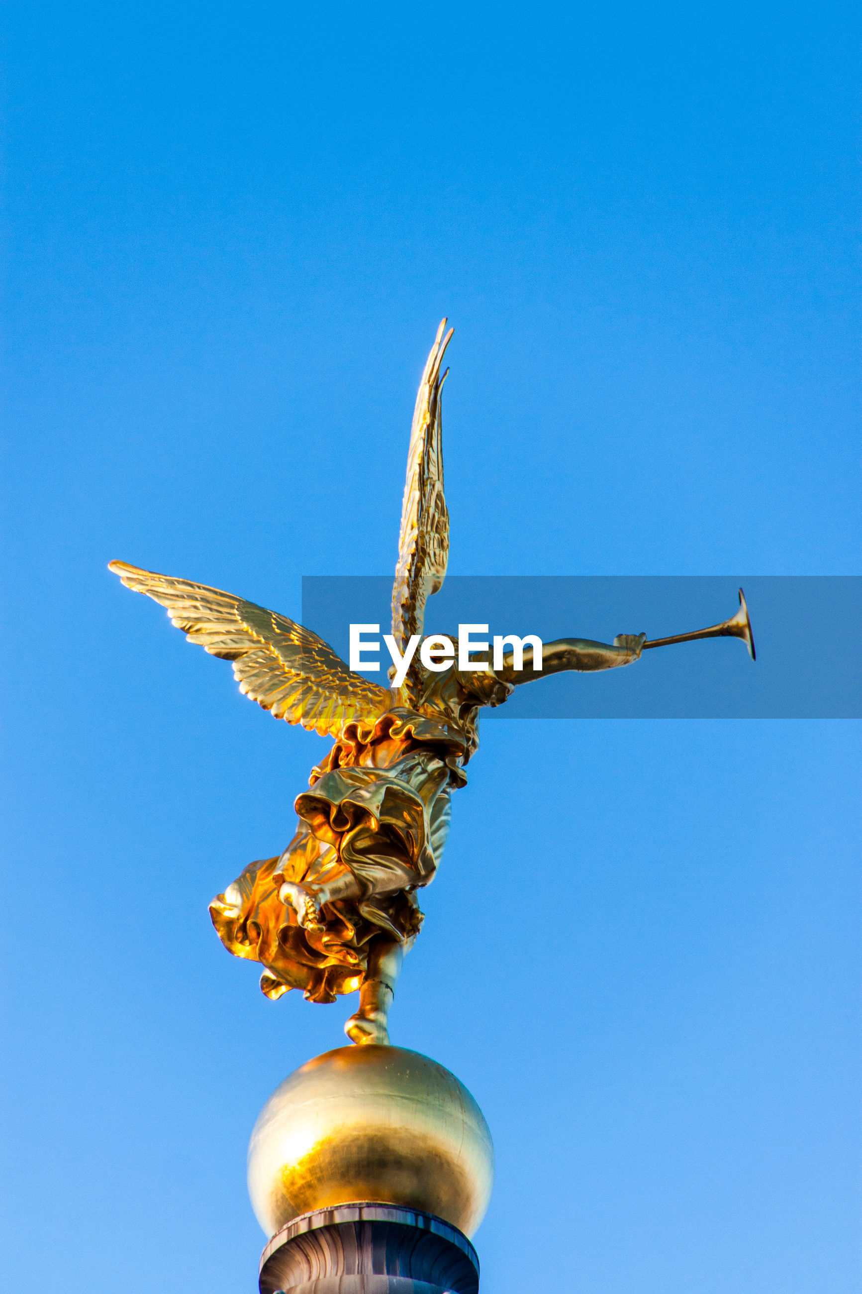 Low angle view of angel statue on dresden frauenkirche against clear sky