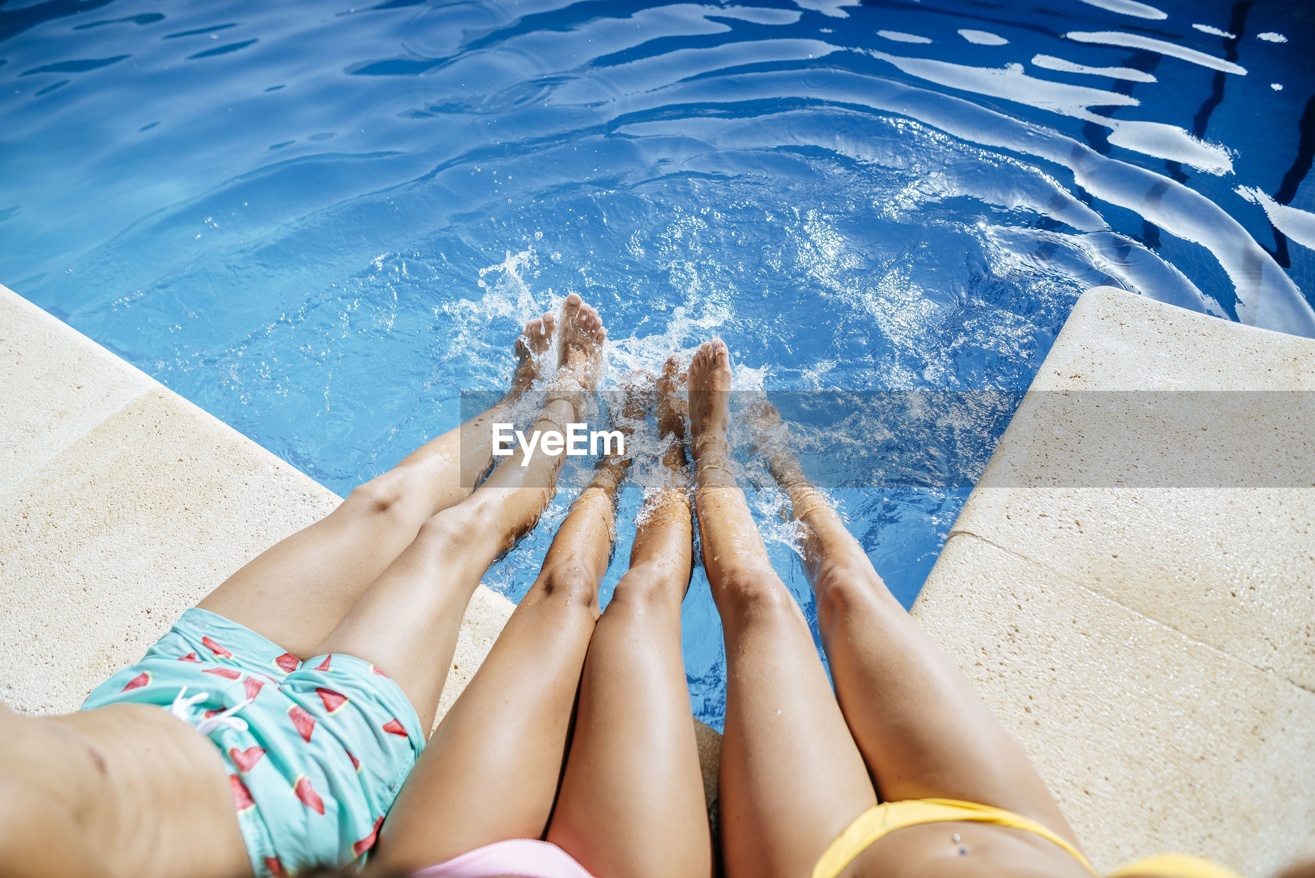 LOW SECTION OF WOMAN LEGS IN SWIMMING POOL AT PARK