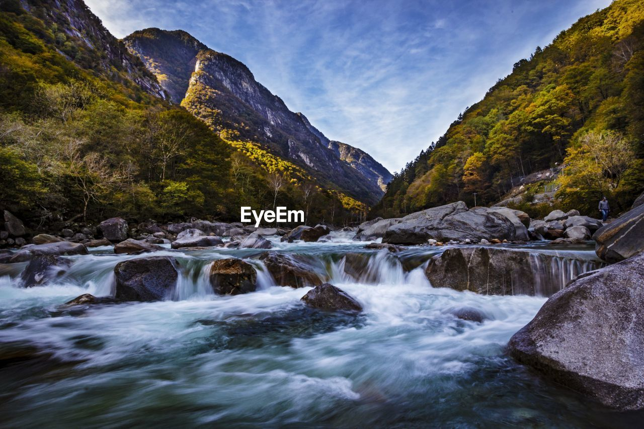 Scenic view of river flowing through rocks against mountains at valle verzasca