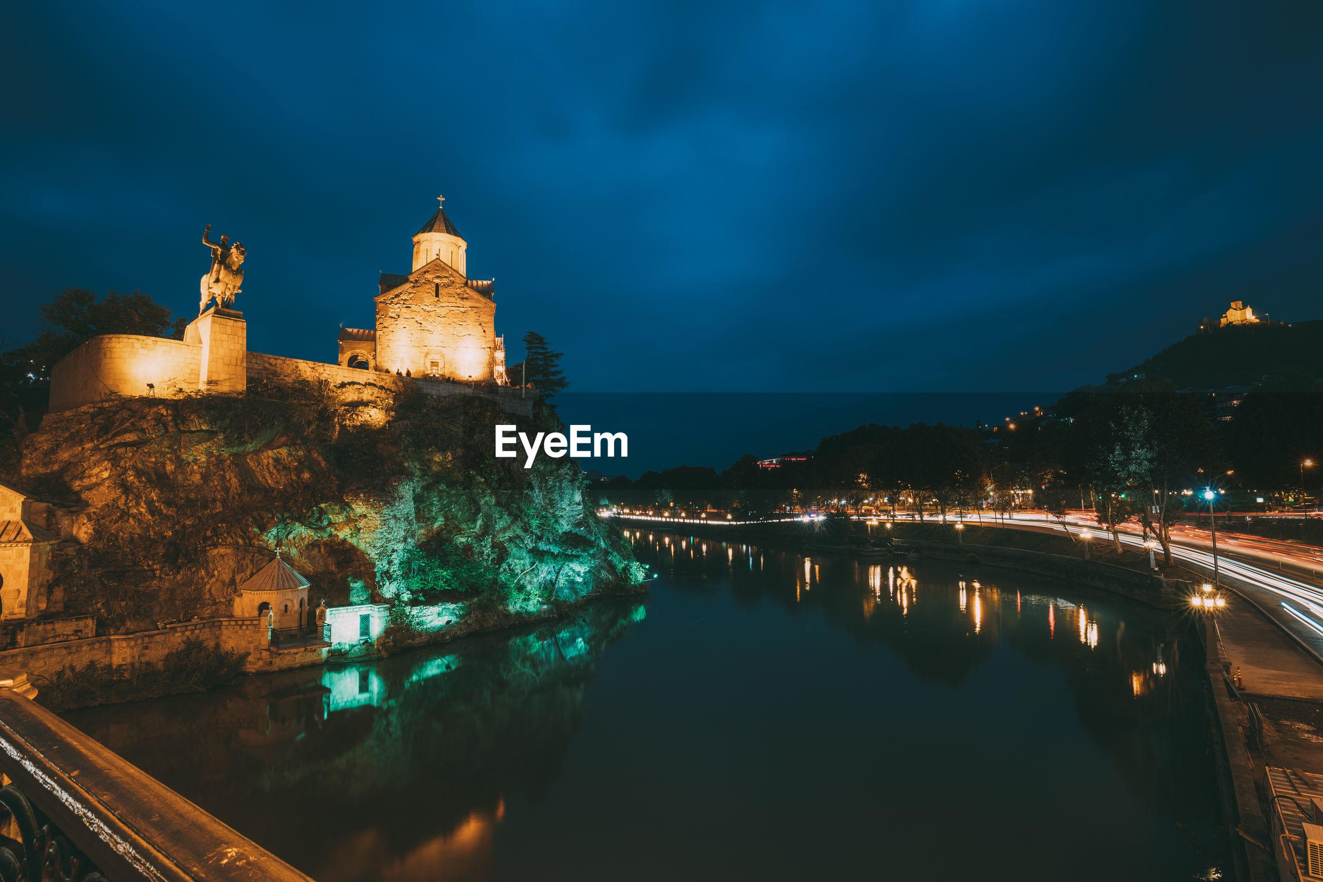 Illuminated historic buildings on mountain at night