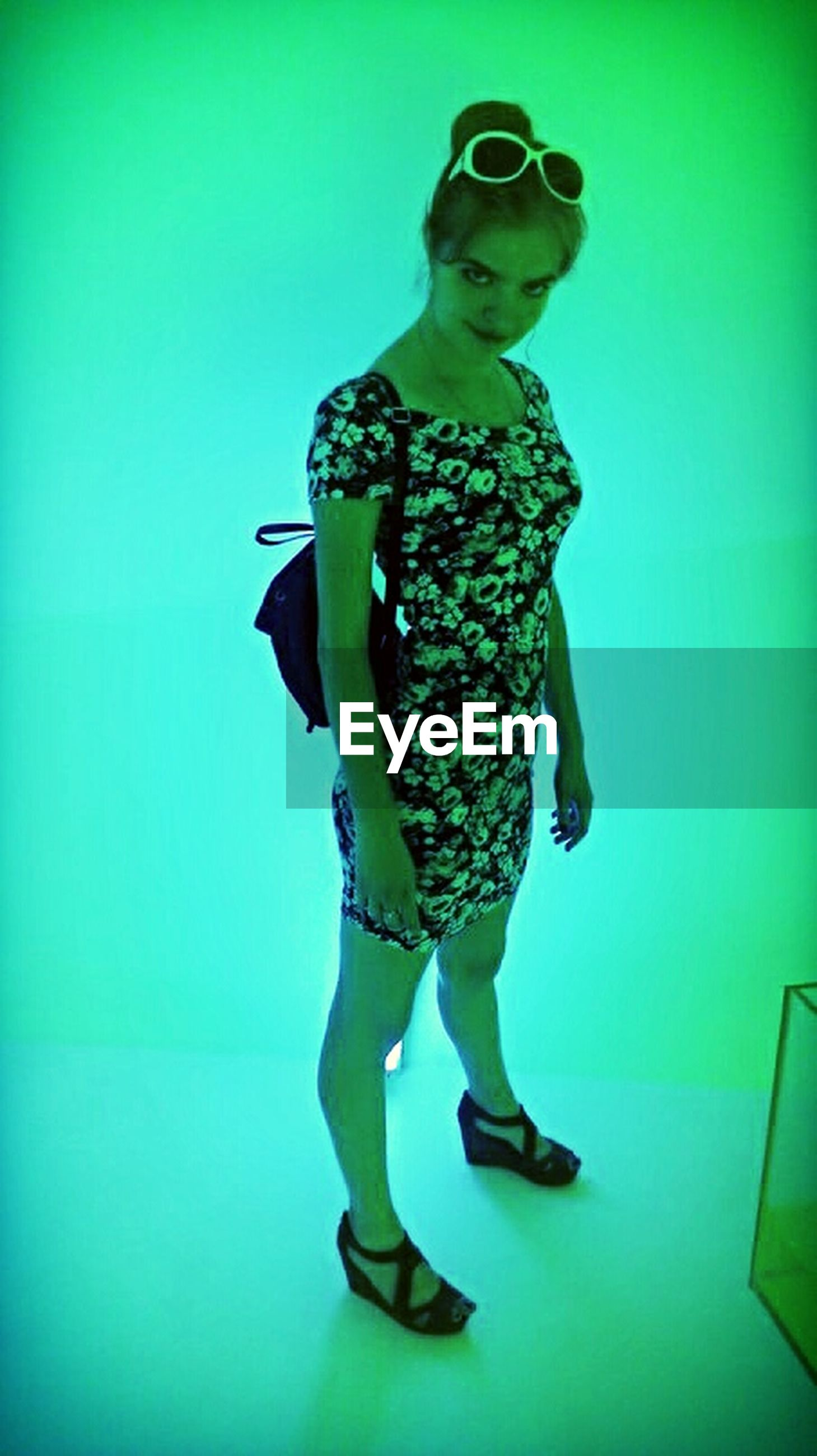 full length, lifestyles, casual clothing, young adult, leisure activity, standing, front view, young women, blue, person, low angle view, fashion, green color, dress, indoors, three quarter length, arms outstretched