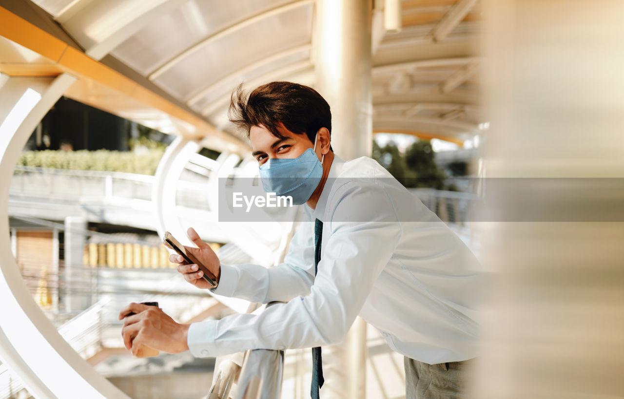 Portrait of man holding smart phone standing on footbridge