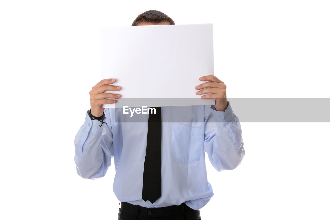 Young businessman covering face with blank placard against white background