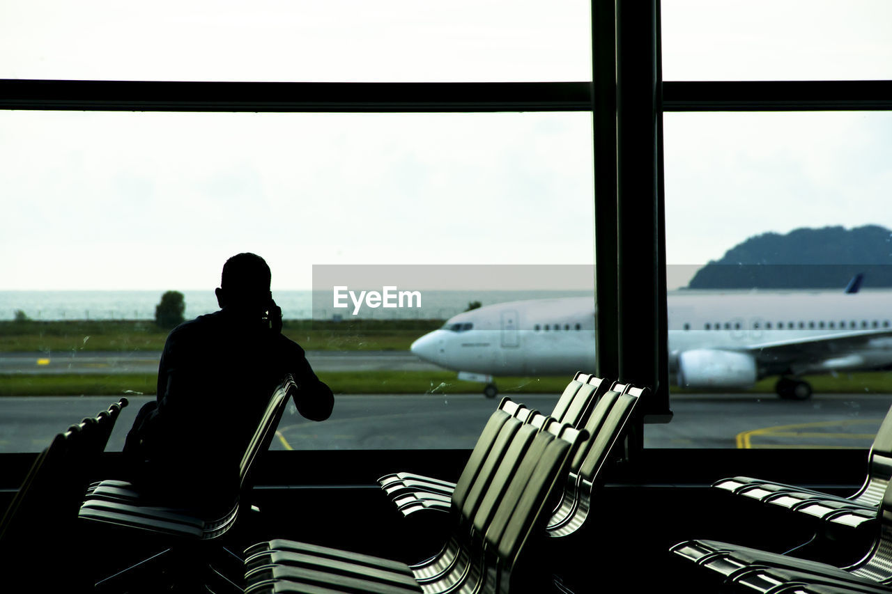 Rear view of man sitting in waiting room at airport