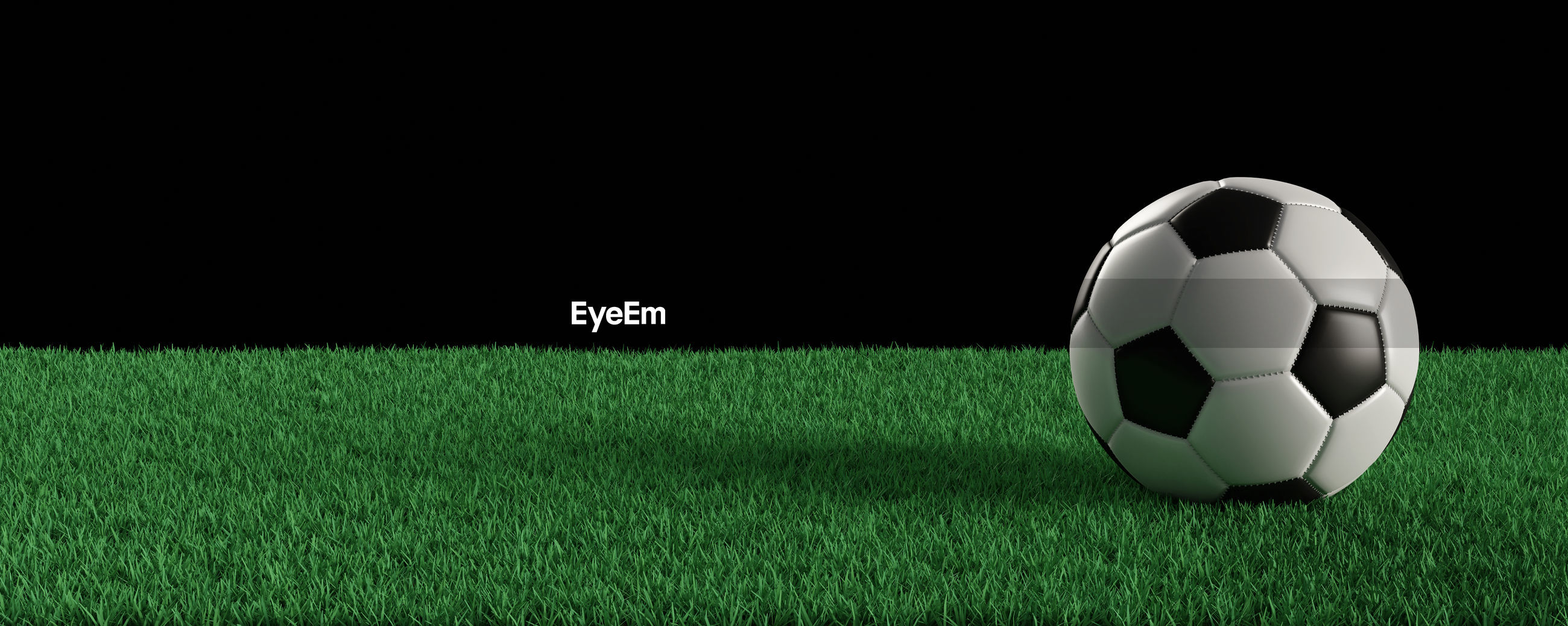 Panoramic view of soccer ball on turf against black background