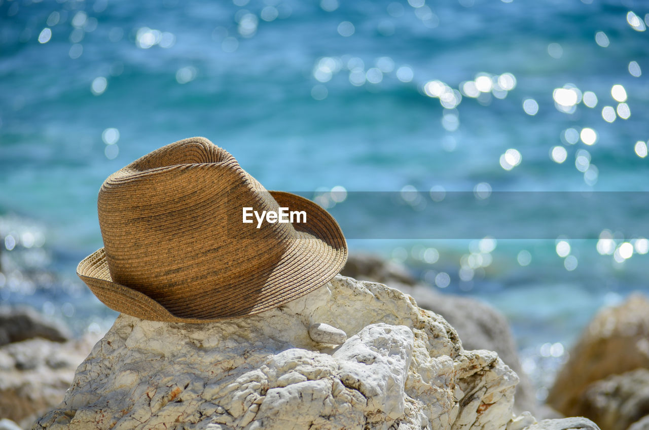 Close-up of sun hat on rock by sea
