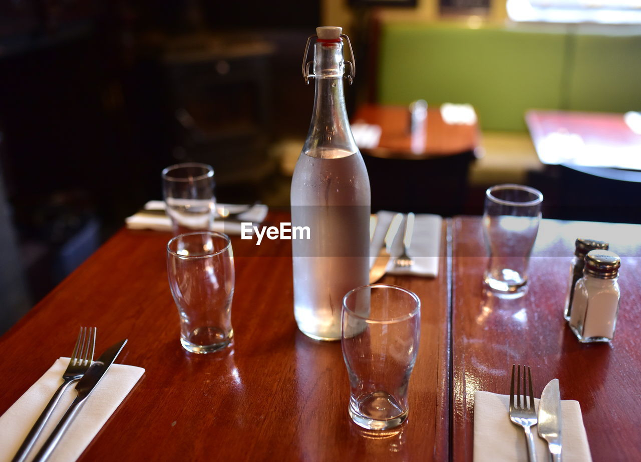 table, drinking glass, indoors, bottle, food and drink, fork, plate, place setting, no people, alcohol, drink, shot glass, close-up, day