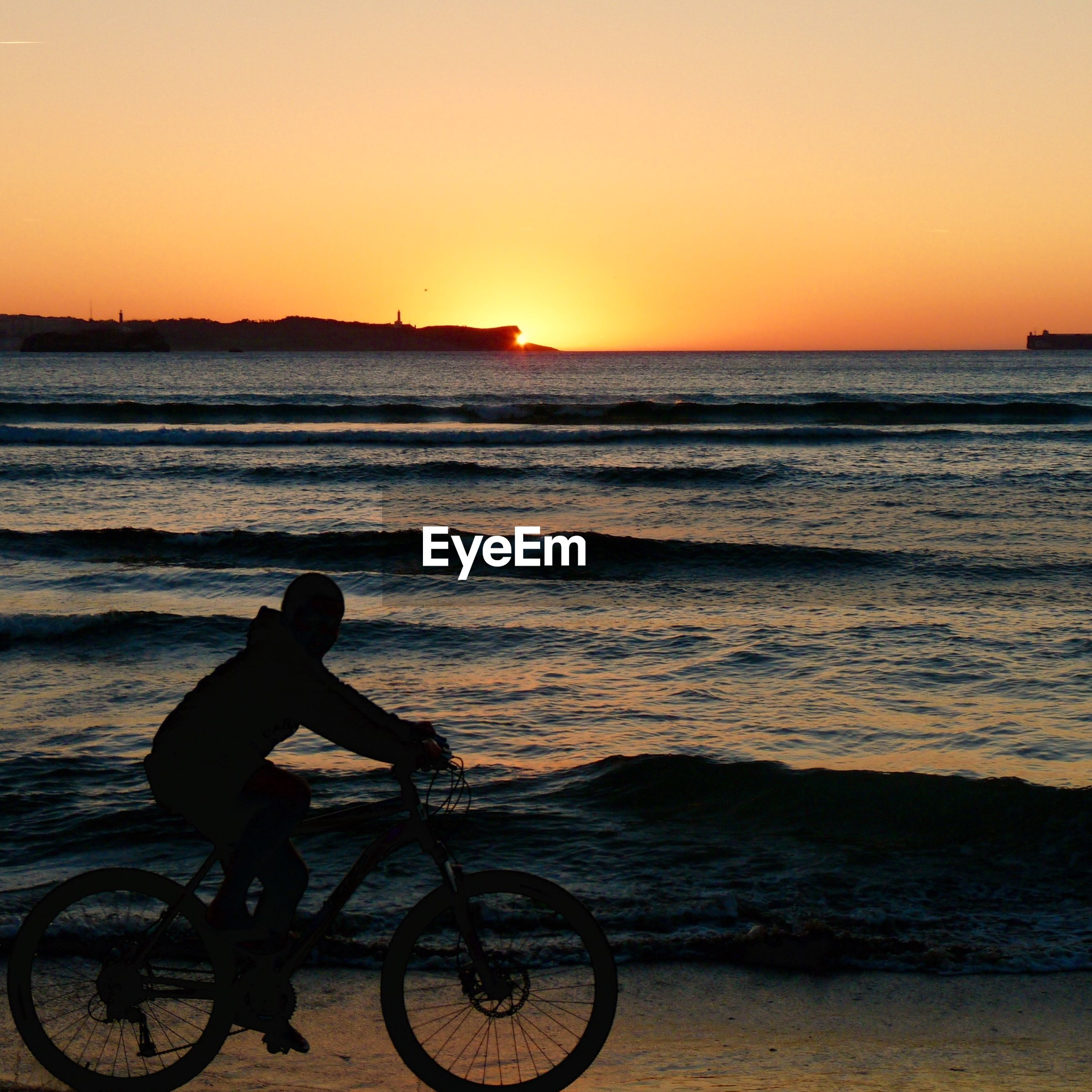 Silhouette person riding bicycle on beach against sky during sunset