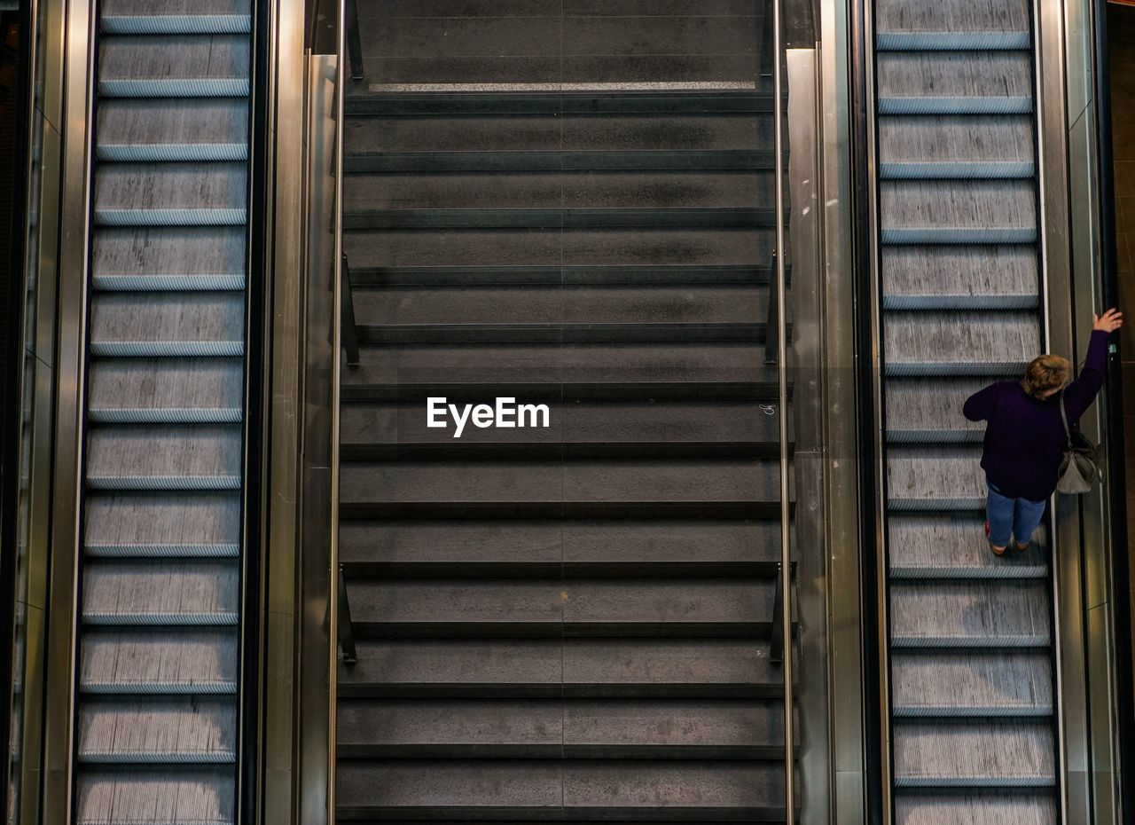 High Angle View Of Woman Standing On Escalator