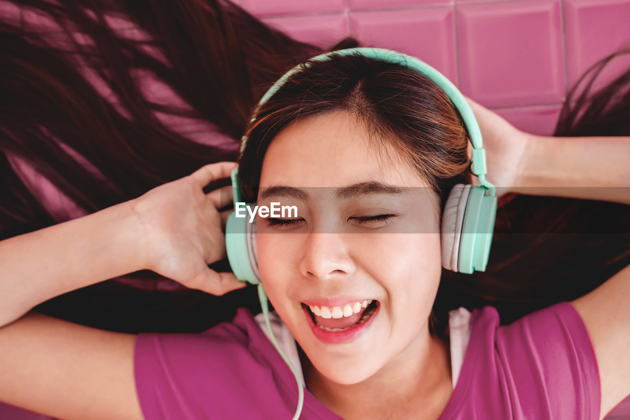 Woman listening to music through headphones against wall