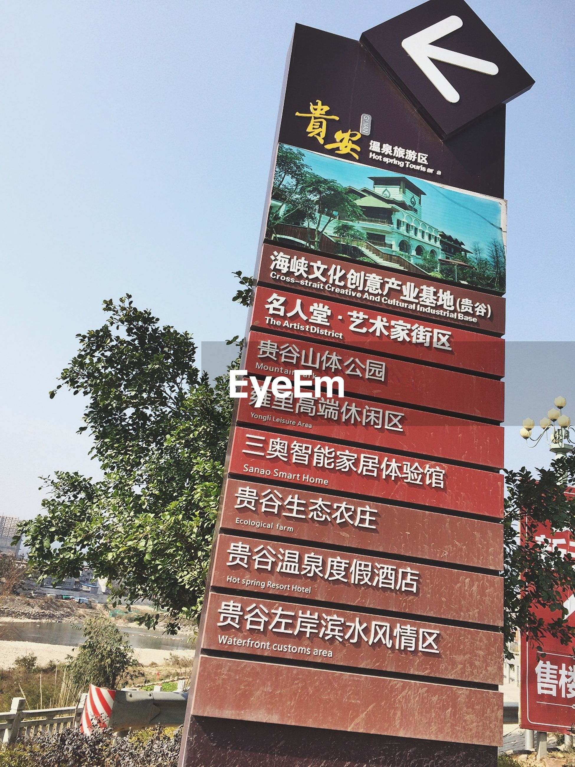text, western script, communication, information sign, sign, information, low angle view, non-western script, clear sky, capital letter, road sign, guidance, tree, directional sign, arrow symbol, built structure, architecture, warning sign, day, building exterior