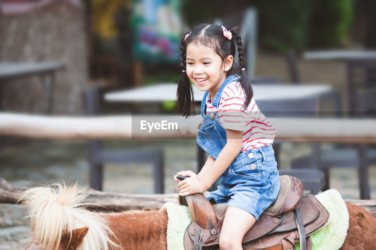 Side view of cute cheerful girl sitting on pony at farm