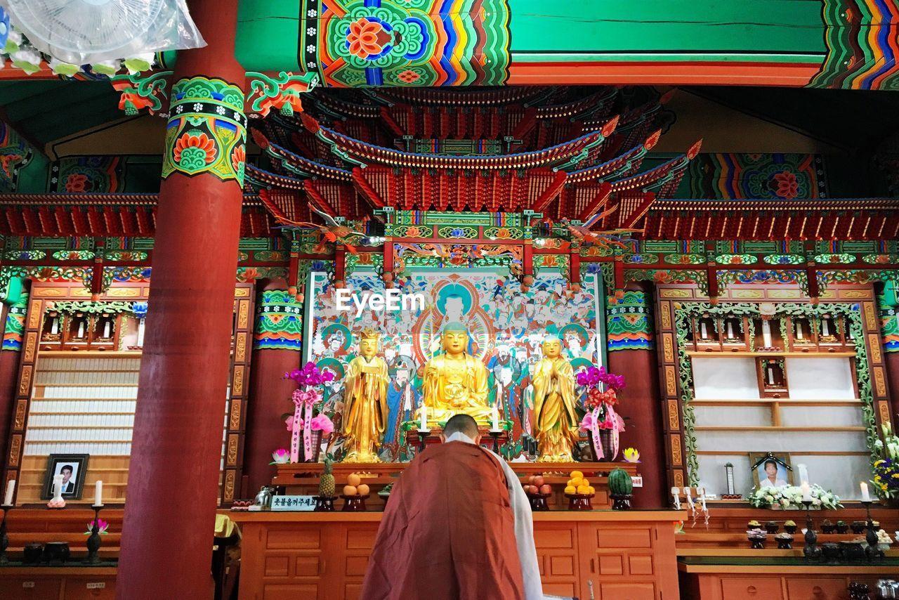Rear View Of A Woman Praying At Buddha