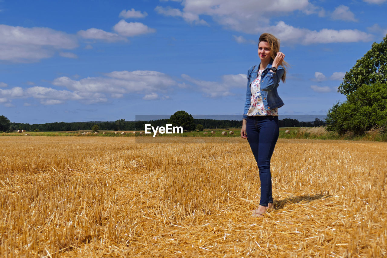 one person, field, land, sky, standing, cloud - sky, plant, casual clothing, young adult, beauty in nature, day, real people, agriculture, nature, lifestyles, landscape, full length, young women, adult, outdoors, beautiful woman, hairstyle