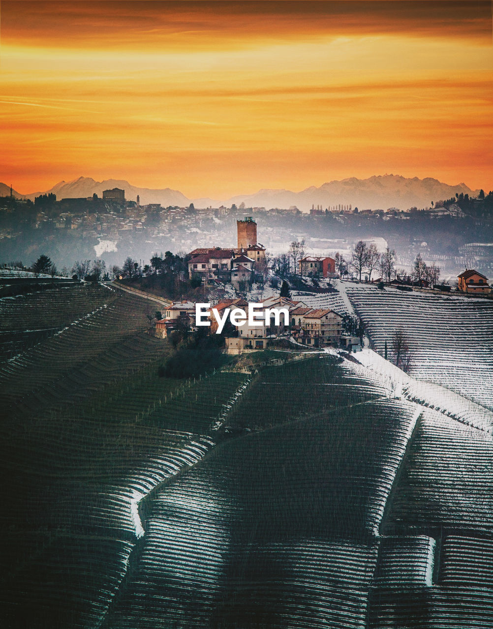 Aerial view of snow covered landscape against sky during sunset