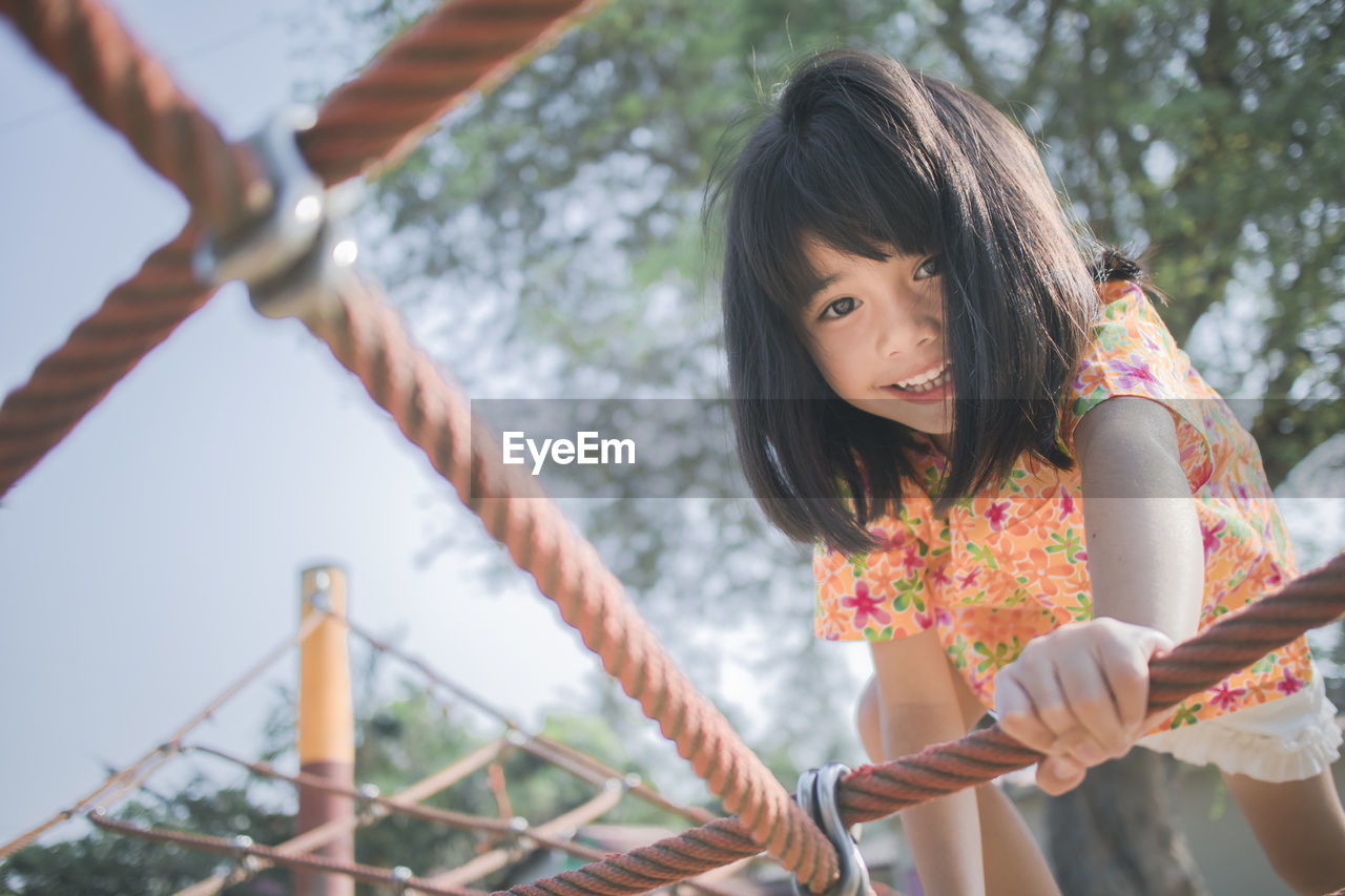 real people, leisure activity, lifestyles, women, one person, girls, females, child, childhood, casual clothing, day, holding, hairstyle, three quarter length, front view, focus on foreground, playground, innocence, hair, outdoors, jungle gym, bangs, outdoor play equipment